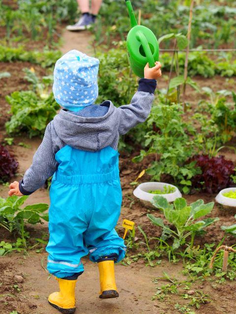 Enkelkind schwingt die grüne Gießkanne auf dem Acker